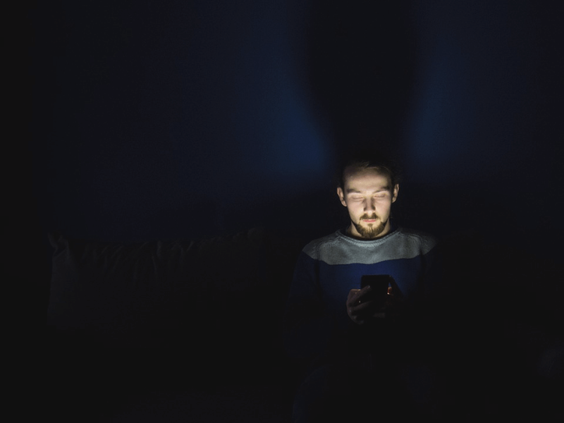 man with face illuminated by smartphone screen in a dark room