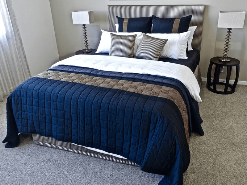 A bed with dark blue beddings and an assortment of pillows