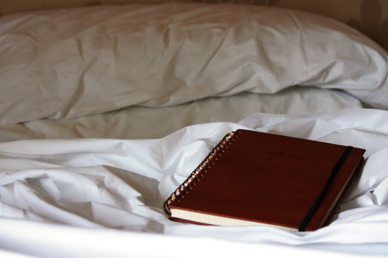 brown ring bound notebook on bed with white sheets