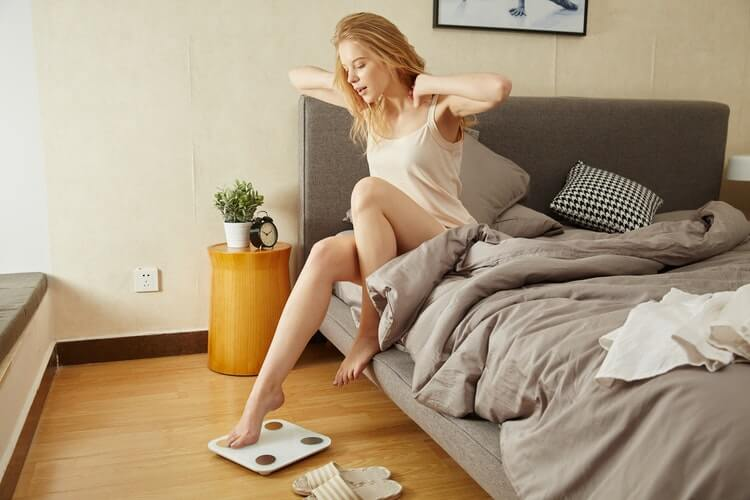 woman stretching arms while sitting on one side of an unmade bed