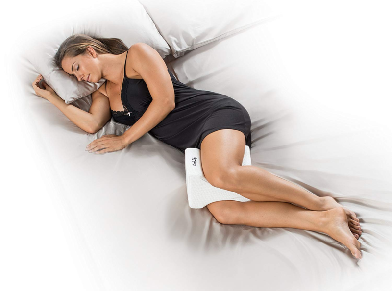 ComfiLife Orthopedic Knee Pillow used by woman in black nightie lying on bed with white sheets