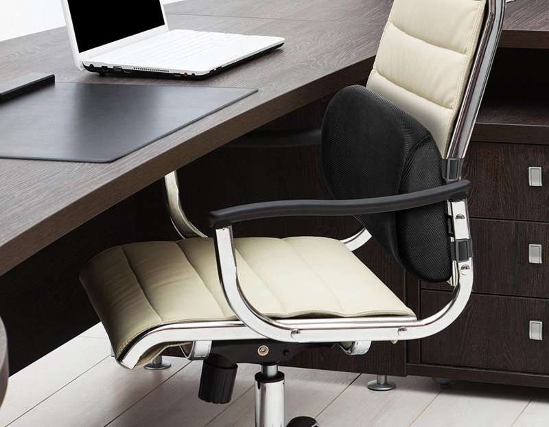 SimplePosture Lower Back Pain Cushion attacked to work chair in front of desk with laptop on it