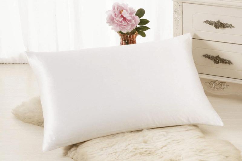 white ALASKA BEAR Silk Pillowcase resting on white fur rug and against gold vase with flower in it