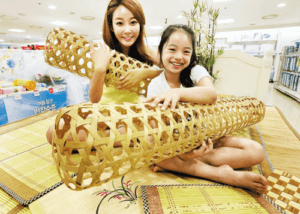 A woman and a young girl holding bamboo wives