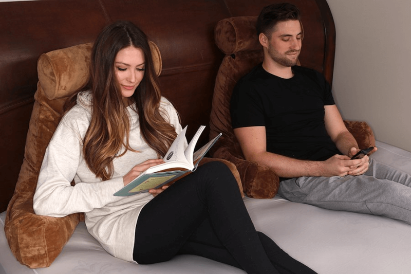 woman reading and man looking at phone side by side both using brown husband pillows
