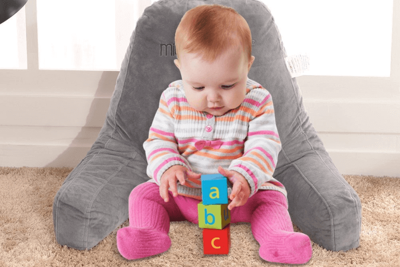 baby in striped shirt and pink tights playing with alphabet blocks and leaning on gray mittaGonG Backrest husband pillow