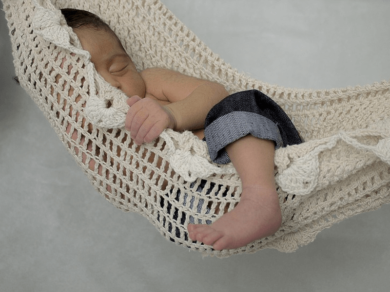 A baby napping on a hammock