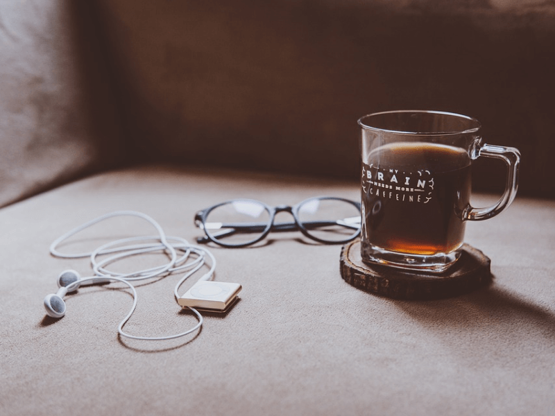 A cup of coffee, glasses, and an mp3 player