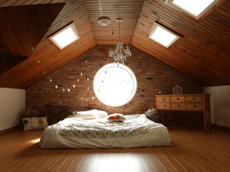 bed laid directly on wooden attic floor underneath a chandelier