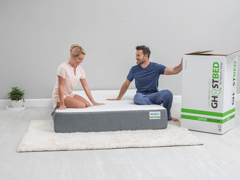 woman and man sitting on GhostBed mattress on floor next to delivery box