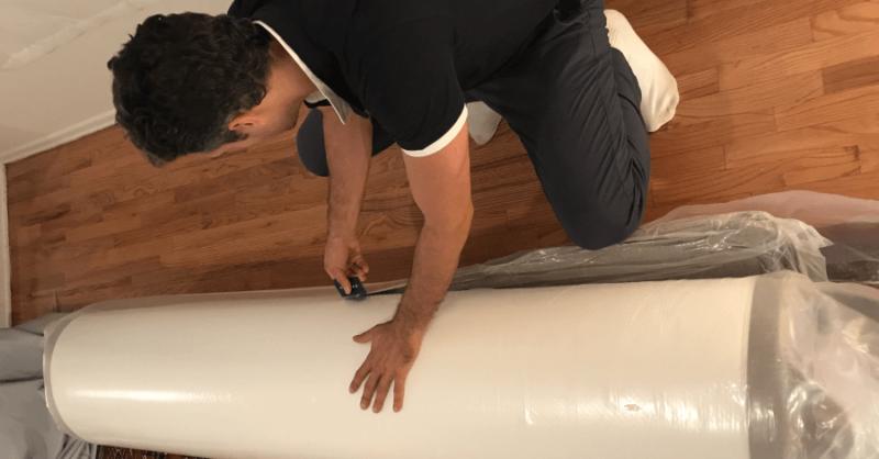 Man unpacking the Nectar mattress on the floor