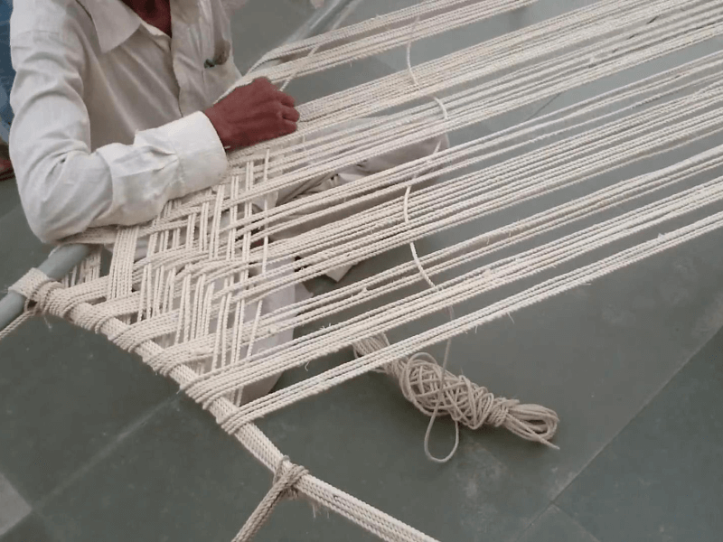 man weaving rope to make a charpai