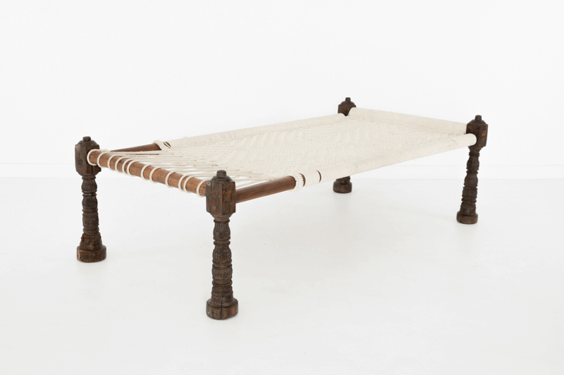 charpai rope bed with wooden frame on white background