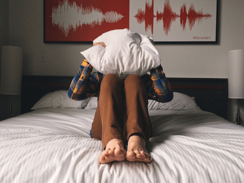 Person on a bed, clutching a pillow over their head, showing signs of anxiety