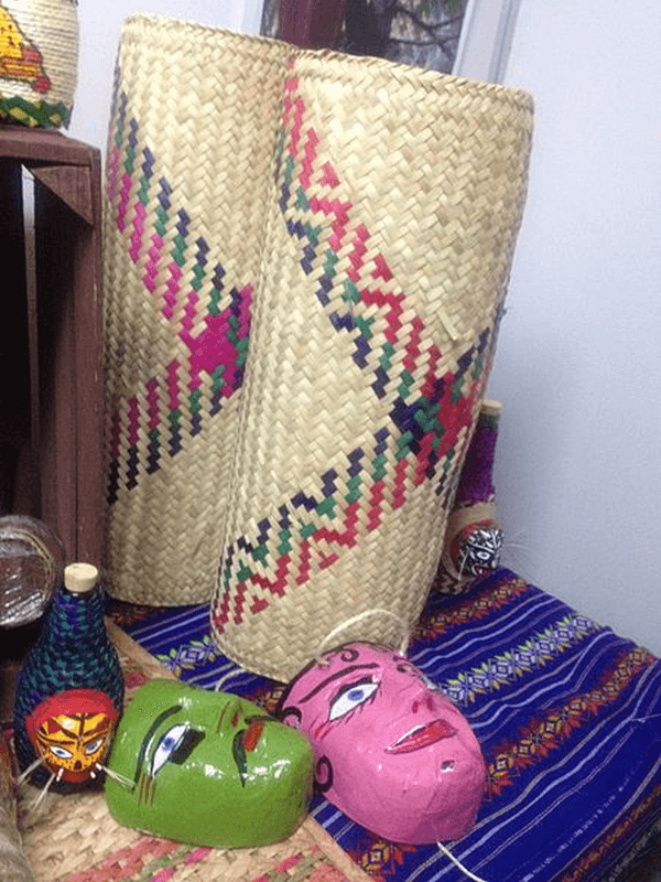 Two rolled up dyed straw mats with assorted novelty items surrounding them