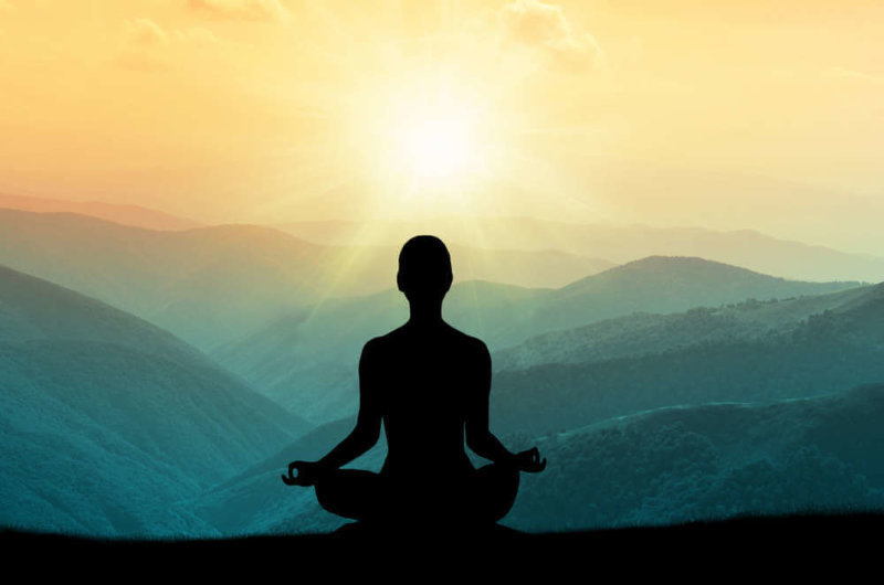 silhouette of person in lotus position looking out onto view of sun and mountains