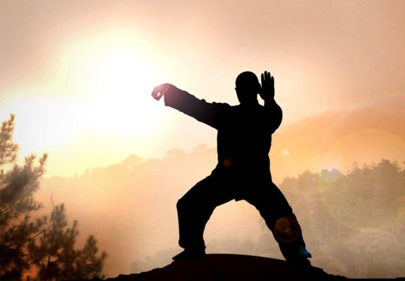 A man practicing qigong meditation atop a mountain