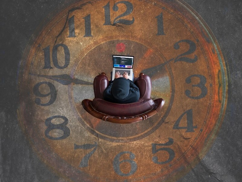 Person sitting with laptop amidst large clock face