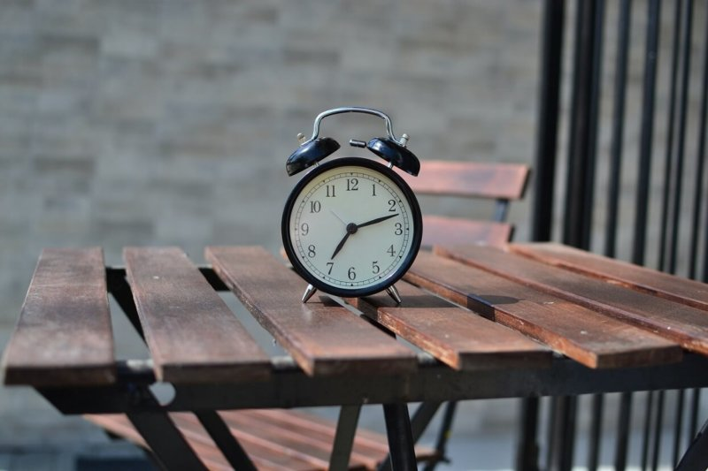 Alarm clock perched on picnic table