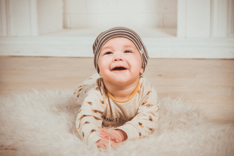 A smiling baby with a bonnet on a rug