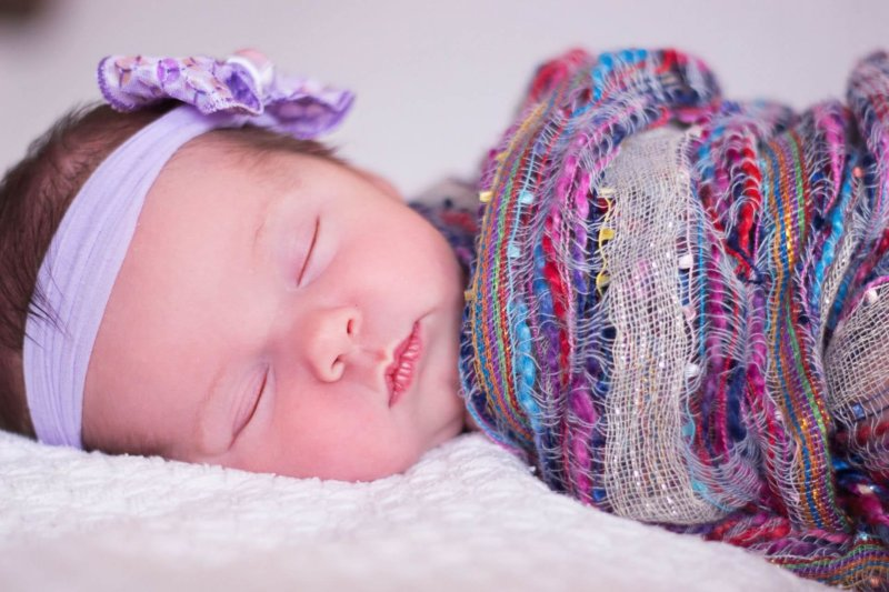 A cute sleeping baby, wrapped in a multi-colored blanket