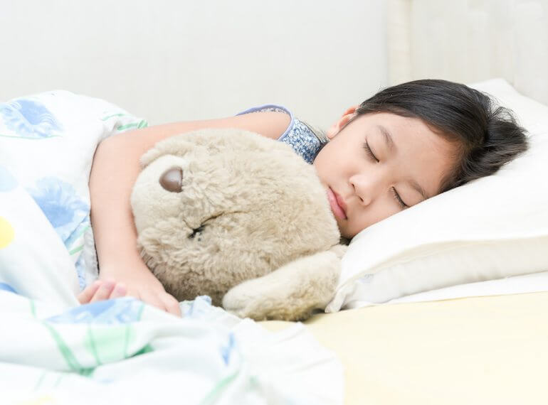 kid asleep in own bed
