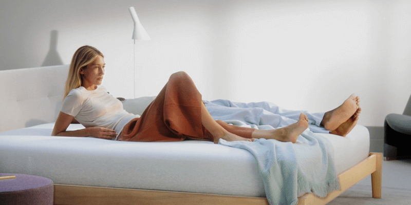 woman lying down with elbows propped up while next to sleeping man on Casper Wave mattress