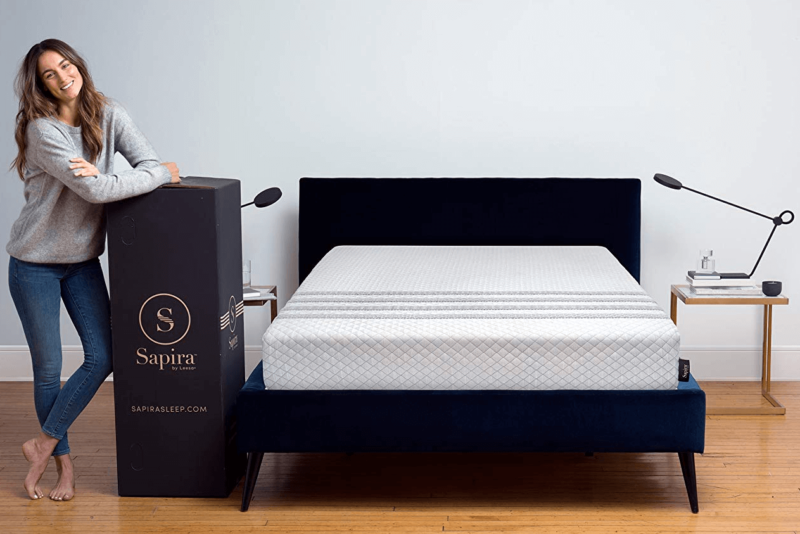Leesa Sapira mattress on black bed frame next to woman and delivery box