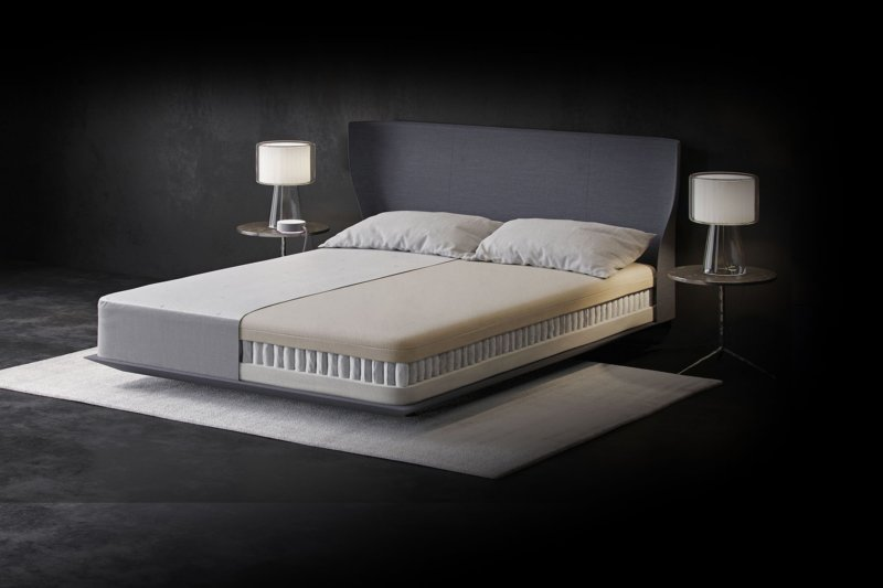 Eight Mars+ smart mattress on white rug between two bedside tables with a lamp on top of each, mattress interior shown