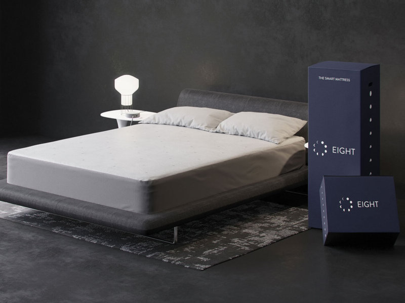 Eight Saturn+ smart mattress against gray background with delivery boxes beside it