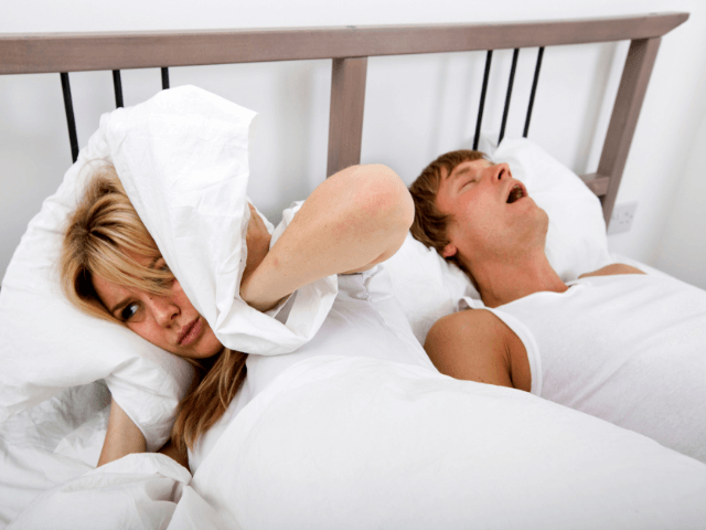 man snoring in bed while woman beside him covers ears with pillow