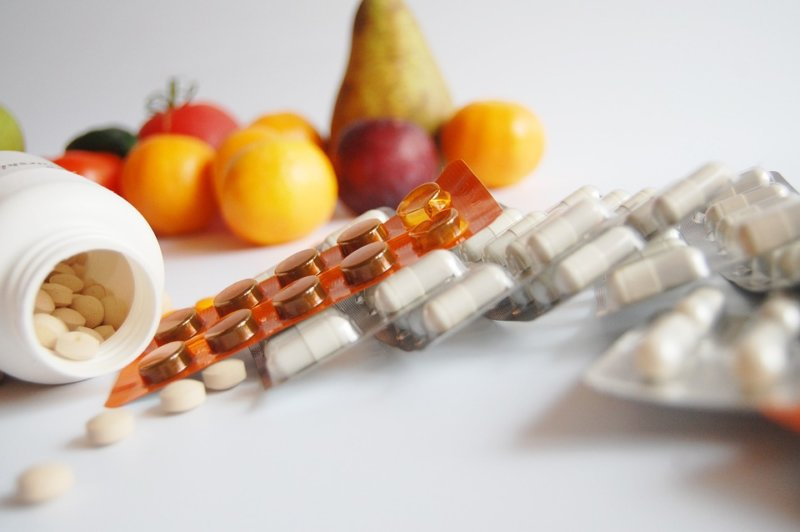 pills against fruits in background