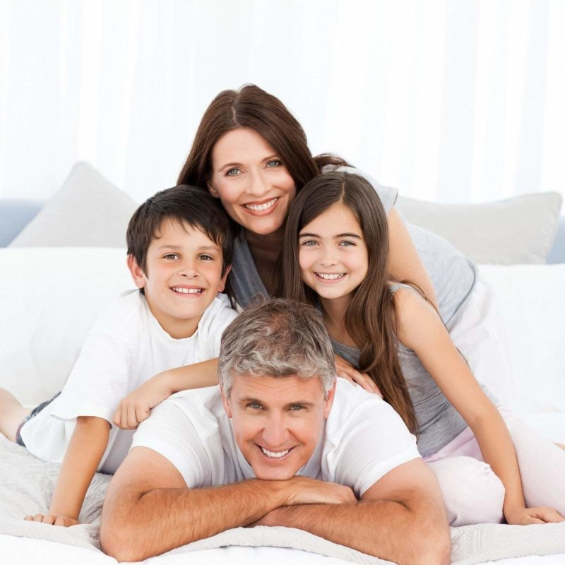 family of four on bed with Mellanni Bed Sheet Set